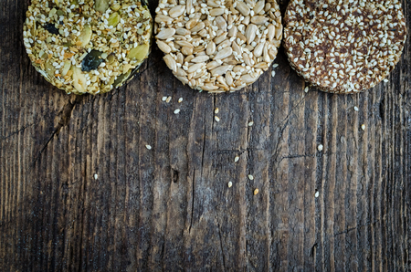 Dessert cereal snacks. Fitness dietary food. Three different kozinaki with sesame, peanuts, sunflower and pumpkin seeds, date on old rustic wooden board. Vegetarian concept. Top view. Copy space. Stock Photo