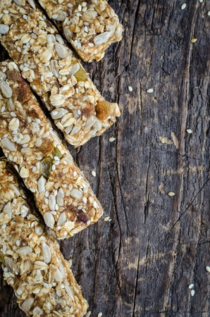 Healthy sweet a dessert snacks. Fitness dietary super food. Energy bars with homemade granola, sesame seeds, raisins on old rustic wooden board. Vegetarian nutrition concept. Top view. Copy space.