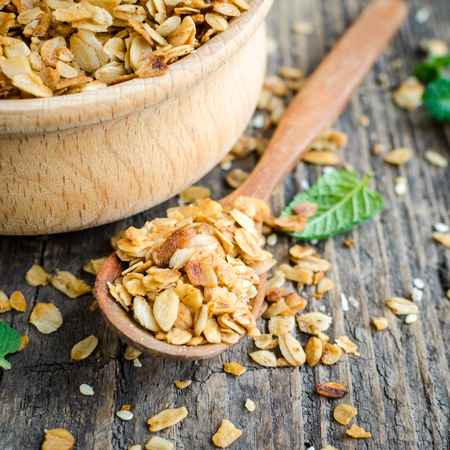 Healthy cereal snacks. Fitness dietary super food. Homemade granola. Baked flakes in wooden bowl on old rustic wooden board. Wooden spoon nearby. Vegetarian vegan nutrition concept. Square. Stock Photo