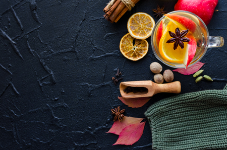 Autumn mulled wine based on white wine with orange, apple and spices cinnamon sticks, star anise, nutmeg, cardamom and clove on black background. Seasonal beverages recipe. Top view. Copy space. Stock Photo