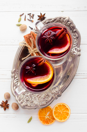 Two glasses of hot red mulled wine or gluhwein with orange, cinnamon sticks and anise on vintage plate on white wooden background. Spicy warm beverage. Seasonal mulled drink. Top view.
