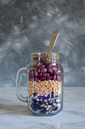 Assortment of dry organic beans and lentils layered in glass jar on marble table. Variety of raw legumes. Balanced diet, cooking, vegetarian and clean eating concept. Healthy food.