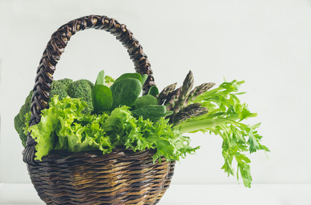 Assorted green vegetables in a basket on white wooden background with place for text. Fresh veggies and greens: spinach, fennel, celery, lettuce, asparagus and broccoli. Copy space. Banco de Imagens