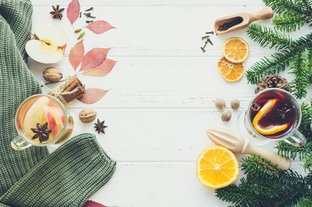 Autumn mulled wine with apple based on white wine ws Christmas mulled wine based on red wine with orange and Christmas spices on white wooden background. Seasonal and holidays. Top view. Copy space. Banco de Imagens