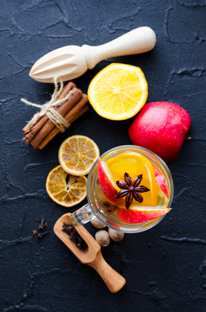 Hot white mulled wine in glass with orange, apple, cinnamon sticks, cardamom and star anise with spices and ingredients on black background. Spicy warm beverage. Seasonal mulled drink. Top view.