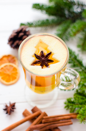 Christmas mulled wine based on white wine with orange and decorations with christmas tree from apple on white wooden background with spices. Seasonal and holidays mulled wine concept.
