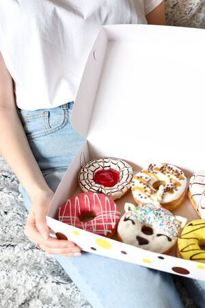 Woman holding box of delicious donuts. Party concept. No diet. Candy bar. Proper nutrition or sweets, dessert fast food, dieting morning concept.