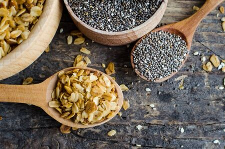 Healthy food. Fitness dietary superfood. Homemade granola. Baked flakes and chia seeds in two wooden bowls and spoons on old rustic wooden board. Vegetarian vegan nutrition concept. Top view. Stock Photo