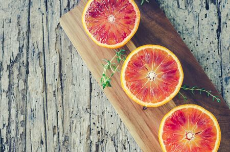 Sliced blood oranges with thyme on wooden board. Citrus background. Cut ripe juicy Sicilian Blood oranges fruits on old wooden textured background. Top view. Copy space. Zdjęcie Seryjne