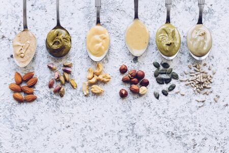 Nuts and seeds butter on a spoons with ingredients. Homemade raw organic almond, hazlenut, cashew, pistachio nuts paste and sunflower and pumpkin seeds butter. Top view. Copy space. Reklamní fotografie