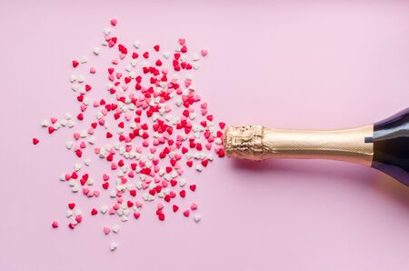 Champagne bottle with hearts confetti on pink background with place for your text. Valentines Day, anniversary or wedding celebration concept. Flat lay. Top view. Copy space. Standard-Bild