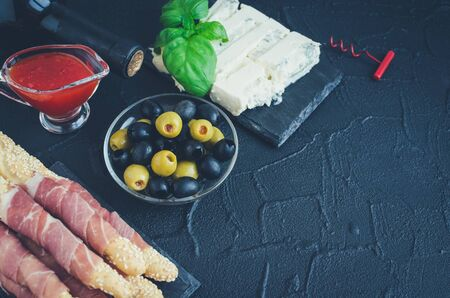 Bottle of wine with antipasti on dark stone background. Grissini breadsticks with prosciutto ham, basil, olives, gorgonzola cheese and chili pepper jam. Italian style party. Copy space. 版權商用圖片