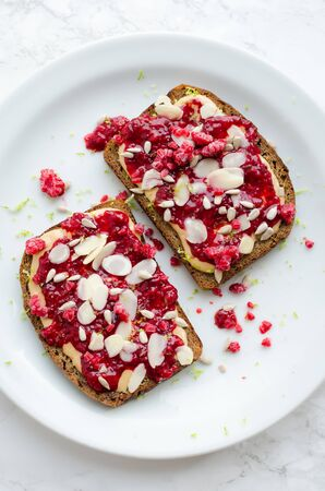 Toasts with peanut butter, homemade raspberry chia jam, walnuts, almonds and sunflower seeds on white marble background. Healthy idea for breakfast toasts. Superfoods and healthy food concept. Top view. Banco de Imagens