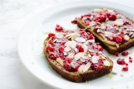 Toasts with peanut butter, homemade raspberry chia jam, walnuts, almonds and sunflower seeds on white marble background. Healthy idea for breakfast toasts. Superfoods and healthy food concept. Banco de Imagens