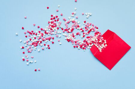 Opened red envelope and many felt hearts on blue background with place for text. Love letter mail correspondence relationship. Valentines day concept. Top view. Copy space.
