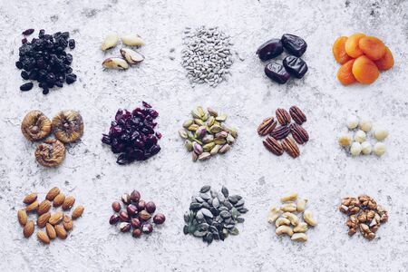 100 calories portion healthy snack of nuts, seeds and dried fruits - pecans, hazelnuts, walnuts, pistachios, almonds, pumpkin and sunflower seeds, cranberries, raisins, figs, dried apricots. Top view. Banco de Imagens