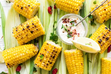 Grilled corn cobs in mexican style with lime, cilantro, chili and sauce on white wooden