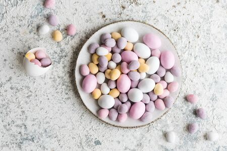 Easter composition with mini chocolate eggs in pastel colors on grey concrete