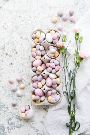 Easter composition with mini chocolate eggs in pastel colors and pink flowers on grey concrete Zdjęcie Seryjne