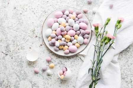 Easter composition with mini chocolate eggs in pastel colors and pink flowers on grey concrete background. Happy Easter Holidays. Top view. Copy space.