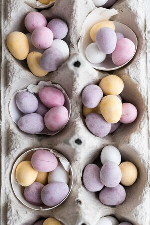Easter composition with mini chocolate eggs in pastel colors on grey concrete background. Happy Easter Holidays. Top view.