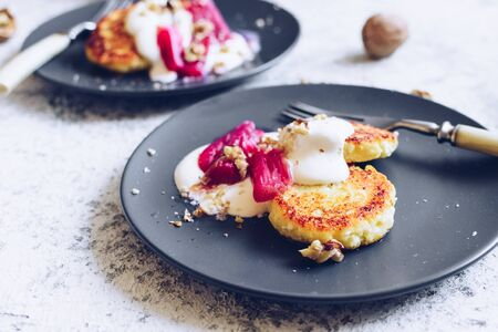 Cottage cheese pancakes served with poached rhubarb on grey background. Gourmet healthy breakfast - cottage cheese syrniki, curd fritters with rhubarb, creme and nuts.