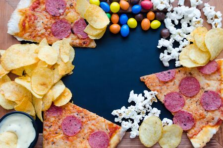 Fast food and unhealthy eating concept. Close up of fastfood snacks: pizza, popcorn, potato chips and candies. Assortment of carbohydrates products bad for figure and teeth. Top view. Copy space.