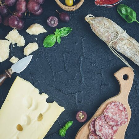 Table full of mediterranean appetizers, tapas or antipasti. Assorted Italian style banquet food set. Delicious snack on party. Chopping board with meat and cheese. Top view. Square. Copy space.