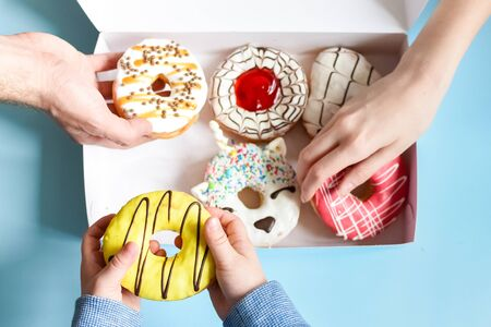 People hands takes donuts from donuts box over blue background. Family eating doughnuts from food delivery. Unhealthy lifestyle concept. Top view or flat lay.