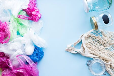 Many disposable plastic bags vs reusable cotton bag and glass jars on a blue Stock fotó