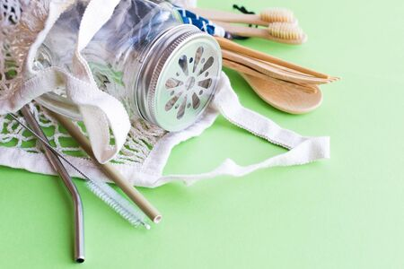 Cotton bag, bamboo cutlery and toothbrush, glass mason jar, metal and bamboo straws on green Stock fotó