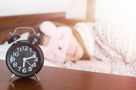 Young woman girl in cute sleep mask and warm pajamas sleep with alarm clock near the bed in the morning. Stock fotó