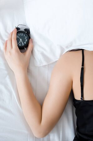 Young woman with pillow over her head with alarm clock in the hand in the morning