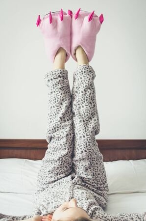 Young woman enjoying sunny morning. Caucasian girl in cute warm pajamas and pink monster foot slippers with big claws lying on the bed at home bedroom after waking up. Good start of the day concept.