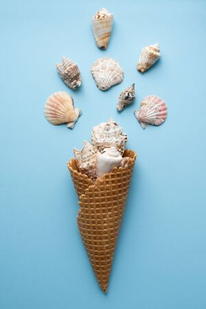 Creative composition with seashell and ice cream cone on pastel blue