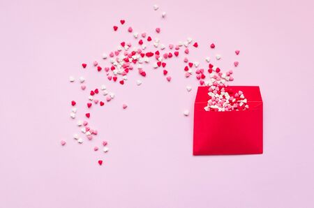 Opened red envelope and many felt hearts on pink
