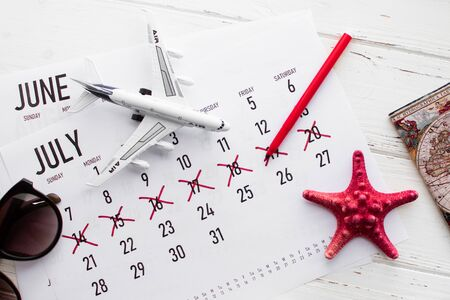 Travel preparation: passport, vacation plan written on calendar and sunglasses on white wooden table. Stock fotó