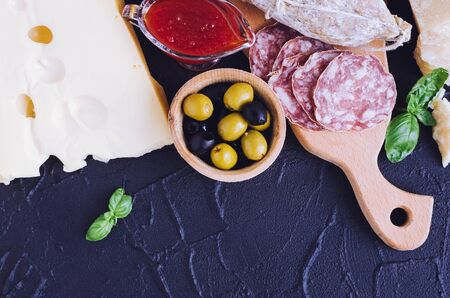 Mediterranean appetizers, tapas or antipasti. Assorted Italian traditional products food set. Delicious snack on party. Chopping board with meat and cheese. Top view. Copy space.