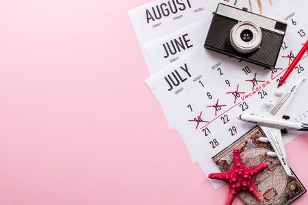 Travel preparation: camera, passport, vacation plan written on calendar and sunglasses on pink