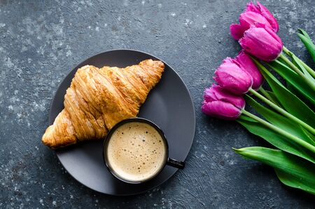 Cup of coffee with bouquet of pink tulips and croissant on black Stock fotó