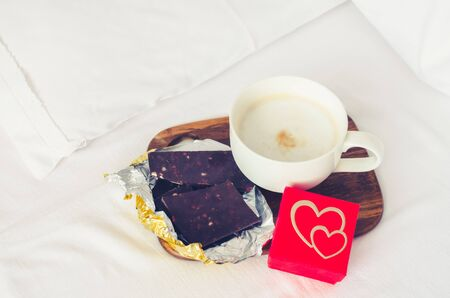 Coffee, dark chocolate and small present on white bed sheet.