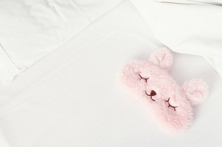 White bedding sheet, blanket and pillows with cute pink sleep mask on the bed