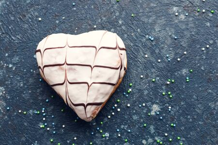 Heart shaped donut with white glaze and chocolate hearts rhythm decoration