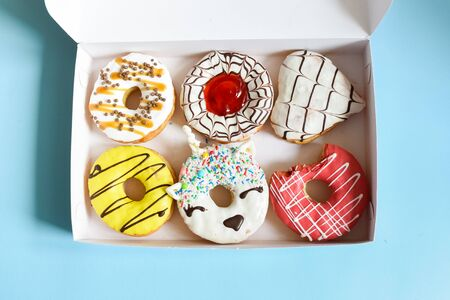 Donuts box over dark background. Trendy doughnut unicorn with white glaze. Top view or flat lay.