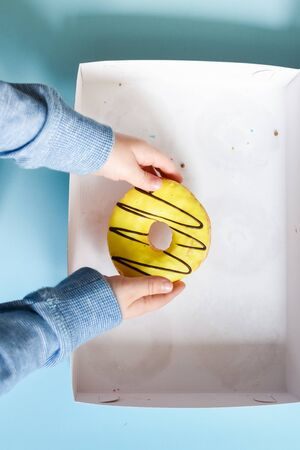 Donut box with a young male child's hand reaching to grab the last yellow banana frosted doughnut over blue background. Family eating donuts from food delivery. Unhealthy lifestyle concept. Top view.