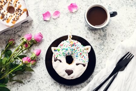 Unicorn donut with cup of coffee and pink roses on white Stock fotó