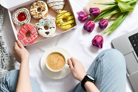 The concept with morning coffee in a romantic style in the bed. Purple tulips flowers, box of donuts and coffee. Woman holding pink strawberry donut. Flat lay. Top view.