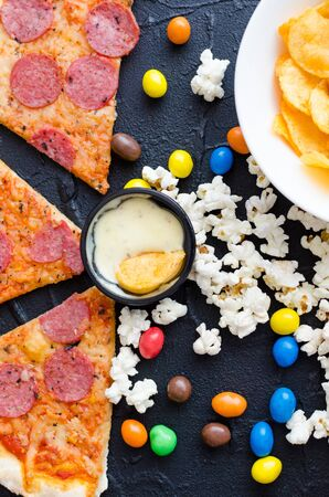 Fast food and unhealthy eating concept. Close up of fastfood snacks: pizza, popcorn, potato chips and candies. Assortment of carbohydrates products bad for figure, skin, heart and teeth. Top view. Stock fotó