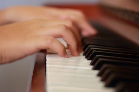 Young boy playing upright piano  Right view photo