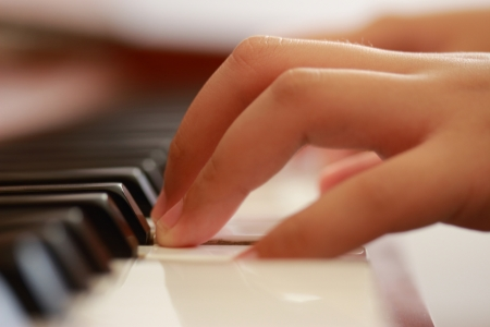 perform: Young boy playing upright piano  Close up view from left